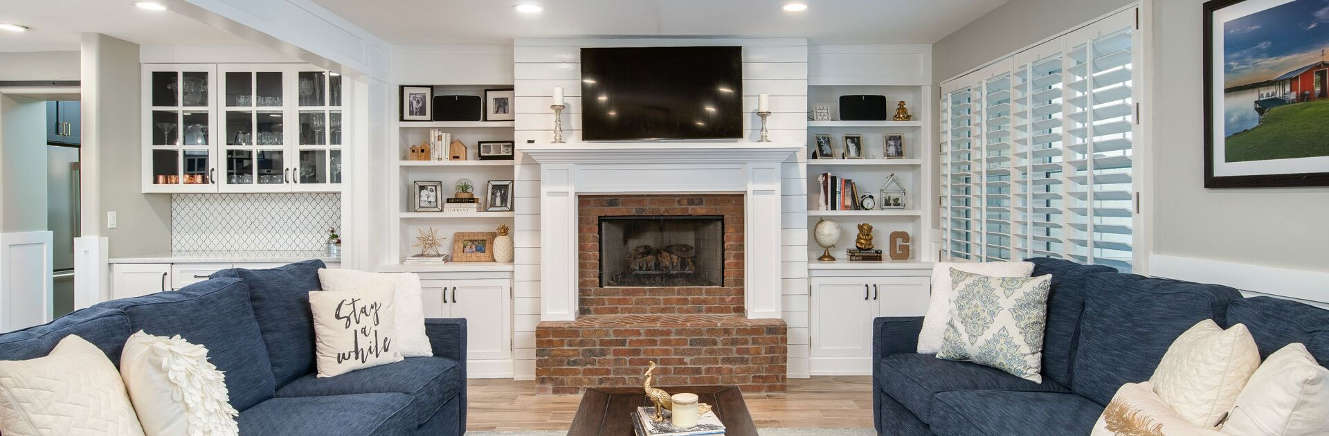home living room with two couches, a fireplace, and built-in bookshelves